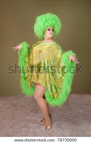 Large drag queen in green dress and wig dances on rug