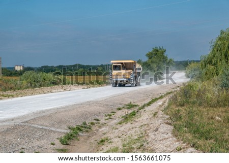 large dump truck loaded with rocks drive on dust road. Mining industry. Heavy equipment. #1563661075