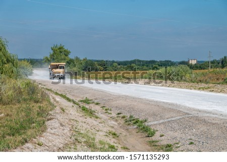 large dump truck loaded with rocks drive on dust road. Mining industry. Heavy equipment. #1571135293