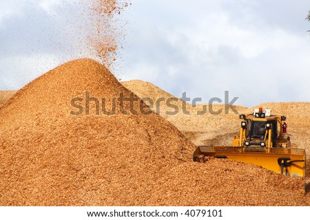 Large earthmover with scoop of wood chips