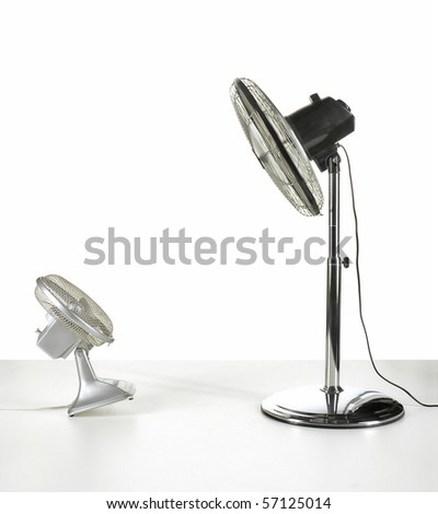 large electric fan blowing over a smaller fan - stock photo