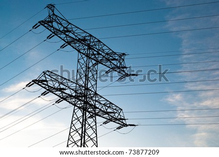 large electricity pylon against blue sky with clouds