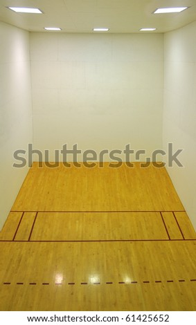Large empty basketball court with a wooden floor and white wooden tile walls with square lights on the ceiling and lots of open blank empty space.