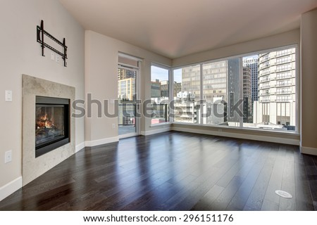 large empty living room with fireplace and hardwood floor