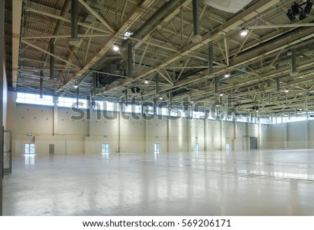 Large empty space in hangar with lights through the windows #569206171