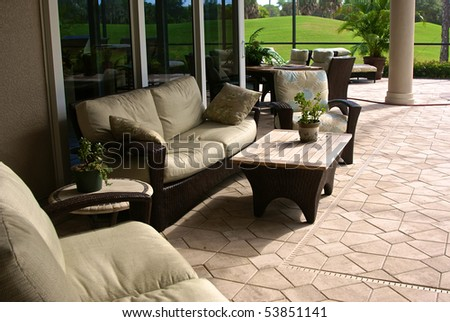 Large enclosed outdoor living area with outside furniture and golf course in background in southwest florida