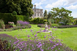 large English garden estate with flower borders and hedges and other garden furniture and design