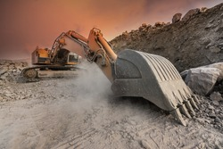 Large excavator extracting stone in a dust cloud in a desert