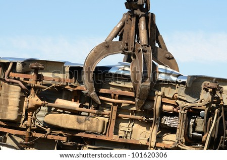 Large excavator with a claw crushing and piling old cars at a metal recycle plant