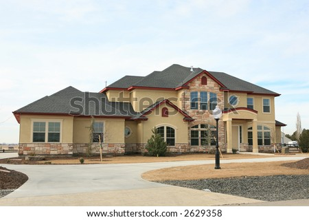 Large expensive modern house yellow stucco and stone