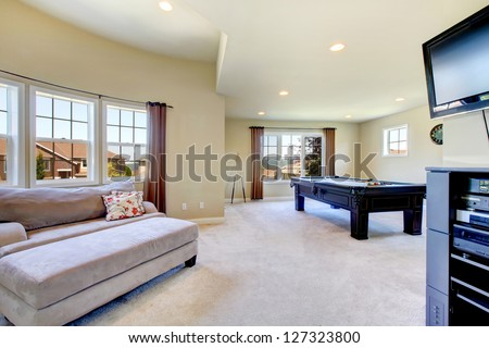 Large family room with pool table, sofa  and tv.