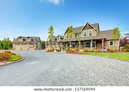 Large farm country house with gravel driveway and green landscape. #127569044