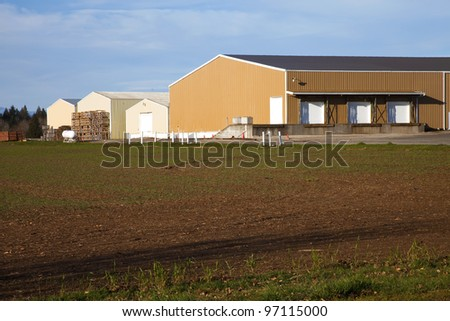 Large farm warehouses, shipping docks and field rural Oregon.