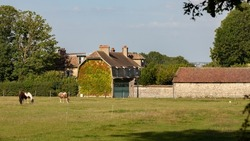 Large farmhouse in a rural countryside setting in northern France. Stone buildings with a facade covered with Virginia creeper and small tiled roofs. Meadows grazed with horses. Oaks ans blue sky