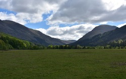 Large field in a valley between two mountain ranges.