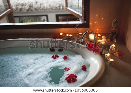 Large Filled Bath with Foam and Flowers. Romantic Atmosphere, Burning Scented Candles and Aromasticks Foto d'archivio ©
