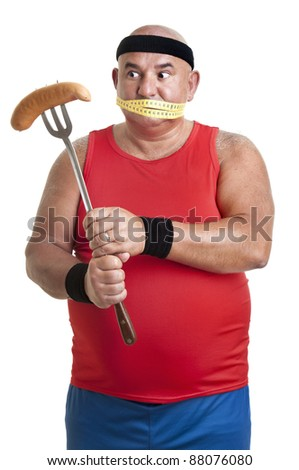 Large fitness man looking at a big sausage isolated in white