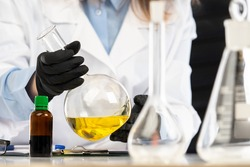 Large flask in the hands of a scientist. laboratory glassware close-up. Yellow liquid in laboratory glassware. Concept - sale of laboratory glassware. Experiments using medical flasks.