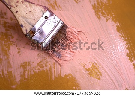 Large Flat Paintbrush with Strawberry Pink Paint on Ochre Yellow Wall