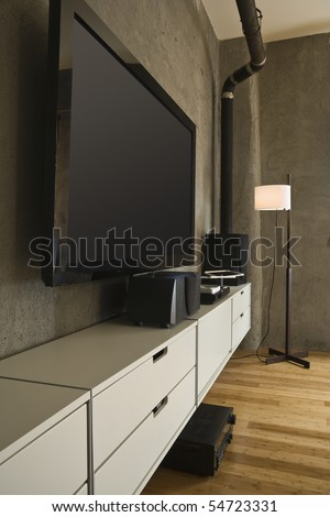 Large flat panel television and entertainment center in a modern loft. Vertical shot.