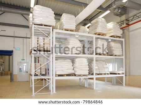 Large food warehouse with sugar sacks on steel shelves