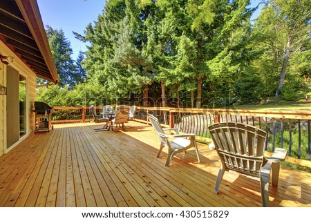Large freshly painted new wooden deck with nice summer green backyard and outdoor furniture.
