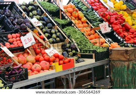 large fruit and vegetable stand with basket full of seasonal fruits in the local market of the city