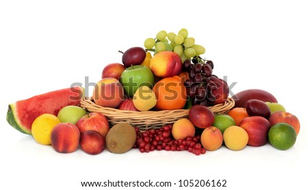 Large fruit collection in a wicker basket and loose over white background.