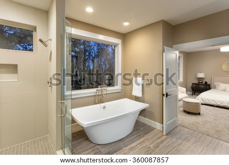 Large furnished bathroom in luxury home with tile floor, shower, bathtub, and view of master bedroom