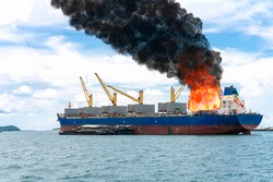 Large general cargo ship for logistic import export goods and other the explosion and had a lot of fire and smoke at sea in bright day