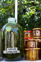 Large glass transparent jar with tincture of green leaves. Georgian Chacha. Liquid organic honey in transparent glass jars. Craft goods with food for sale