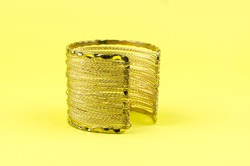 Large gold bracelet on a yellow background.