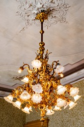 Large golden chandelier with floral shades and lamps in a floral style, under the ceiling with stucco.
