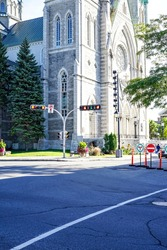 Large gothic style stone catholic cathedral, crossroads, street signs and traffic lights, bright sunny background, Old Longueuil, Montreal, Canada
