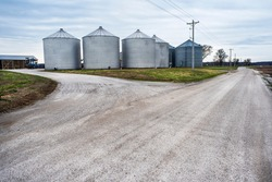 Large grain storage bins on farm next to gravel country road in rural America. farming, farmers, food, crops, storage, silos, silo, corn, grain, soybean, containers, store, dry