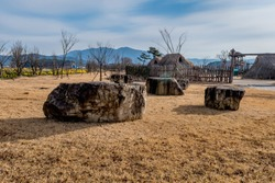 Large granite boulders on ground in front of recreated neolithic village in rural park.