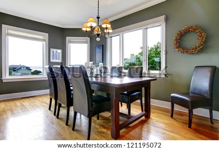 Large green dining room with leather chairs and large windows. #121195072