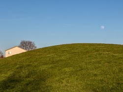 Large green grass hill at sunset with house behind it and moon rising in the blue sky at sunset