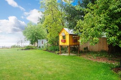 Large green spring grassy back yard with a view of the ocean and yellow kids tree house, play ground.