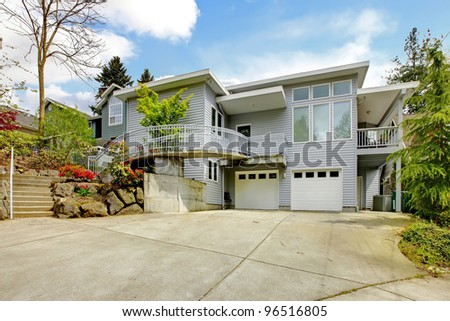 Large grey house exterior of modern home with large parking lot.