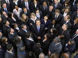 Large group of business people surrounding man looking up elevated view
