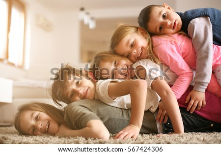Large group of children lying at floor and having fun. Looking at camera. #567424306