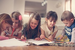 Large group of children write their homework at home.