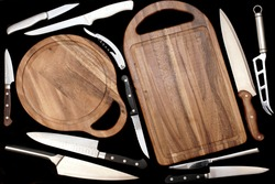 Large Group Of Cookware Isolated On Black Background. Many Kitchen Knives And Cutting Board on Black Table. Collection Of Different Utensils For Cooking Food, Abstract Pattern. Set Of Cookware Objects