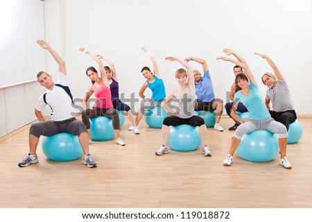 Large group of diverse people in a pilates class exercising in a gym practicing balance and control