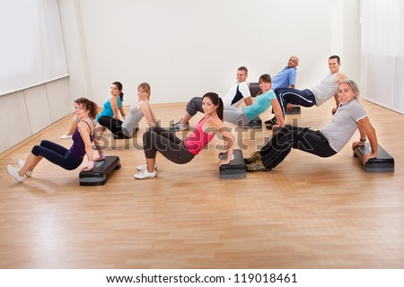 Large group of diverse people working out together in a gym doing balance and muscle control exercises with copyspace