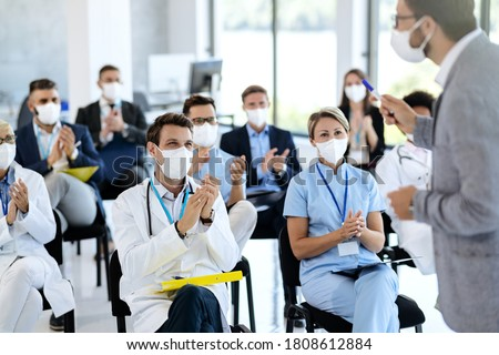 Large group of doctors and business people with protective face masks applauding while attending an educational event at conference hall. Focus is on male doctor.