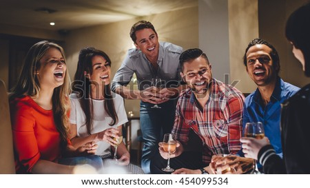 Large group of friends enjoying a glass of wine together in a bar.  #454099534