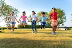 Large group of happy Asian smiling kindergarten kids friends holding hands playing and jumping together during a sunny day in casual clothes at city park. Multi-ethnic children group, outdoor.