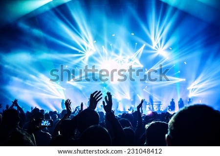 Large group of happy people enjoying rock concert, clapping with raised up hands, blue lights from the stage, new year celebration concept